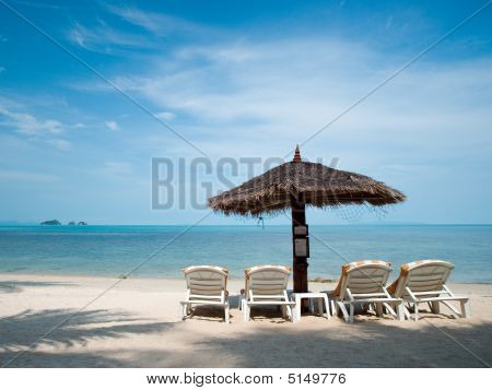 View Of Four Chairs And Umbrella On The Beach