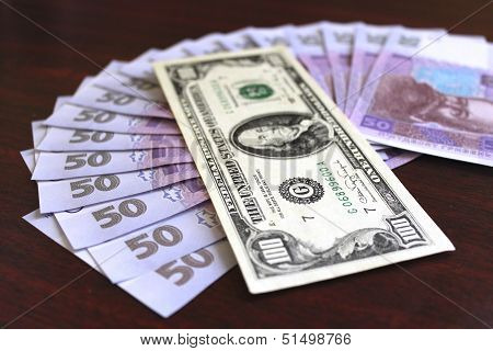 dollar and grivnas banknotes on dark background