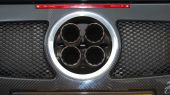 Exhaust of a sport car in a round silver cirlce iwth 4 exhaust pipes and breaking lights visible poster