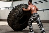 Muscular Man with Truck Tire doing style workout turning tire over poster