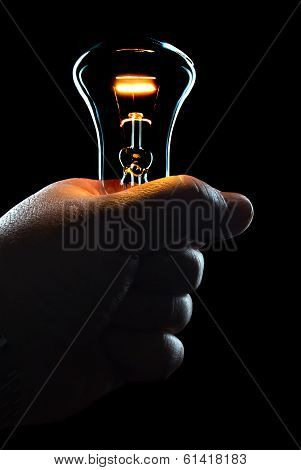 hand with a shining electric bulb