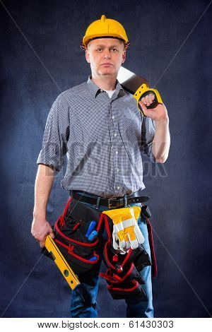 Construction worker holding a spirit level and saw