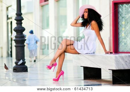 Portrait of a young black woman model of fashion wearing dress and sun hat with afro hairstyle in urban background poster