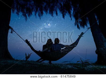 Couple relaxing in a hammock and enjoying starry sky
