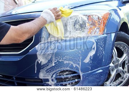 Man's hand washing headlight on car with yellow rag poster