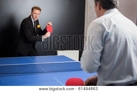 Businessman play tennis with opponent in office poster