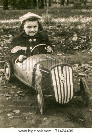 LODZ, POLAND, CIRCA FIFTIES: Vintage photo of little girl in a toy car