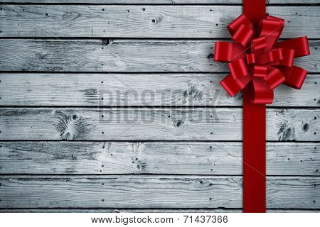 Red christmas bow and ribbon against digitally generated grey wooden planks poster