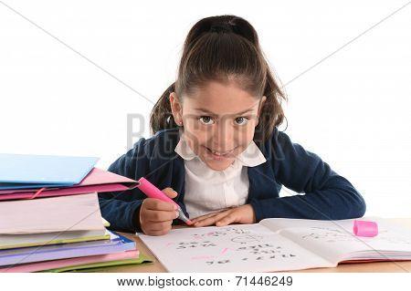 Sweet Happy Latin Child Sitting On Desk Doing Homework And Smiling