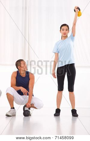 Asian Man Looking Woman Doing Kettle Bell Crossfit Exercise