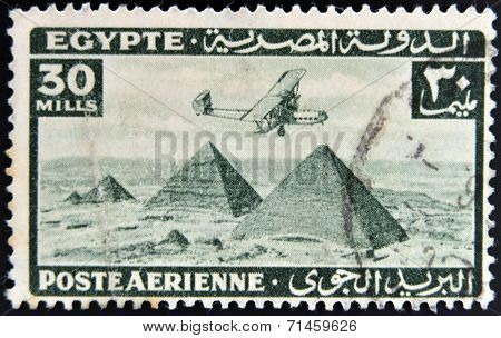 EGYPT - CIRCA 1946: stamp printed in Egypt shows plane over Pyramids at Giza circa 1946