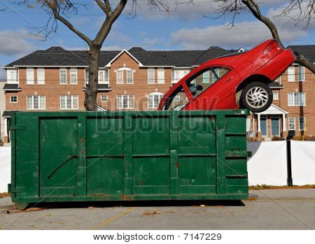 Red car thrown in a green dumpster