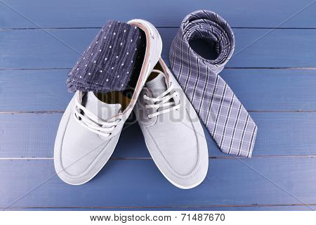 Top-Siders, socks and tie on dark blue wooden background
