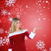 Pretty girl presenting in santa outfit against red snow flake pattern design poster