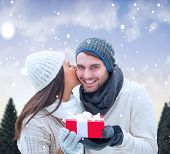 Winter couple holding gift against snowy landscape with fir trees poster