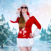 Cool santa girl wearing sunglasses against snowy landscape with fir trees poster