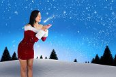 Pretty girl in santa outfit blowing against snow falling on fir tree forest poster