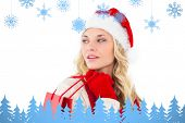 Festive blonde holding shopping bags against snowflakes and fir trees in blue poster