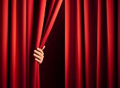 male hand in the act of disclose the scene shifting the red curtain poster