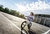 Cute little girl riding fast by bicycle in public park poster