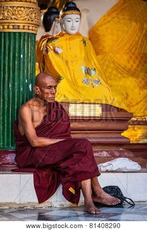 YANGON, MYANMAR - JANUARY 3, 2014: Ascetic Buddhist monk meditating in Shwedagon Paya pagoda