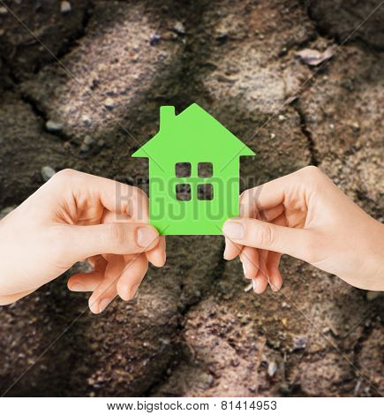 home, farming, energy saving, people and family concept - closeup of woman and man hands holding green house over ground background