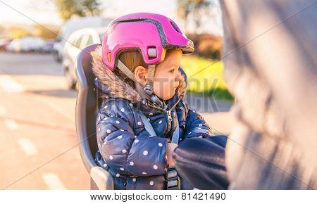 Little girl with helmet on head sitting in bike seat