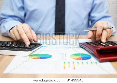 Financial Specialist Is Working With Calculator And Computer To Analyze A Lot Of Data On Financial R