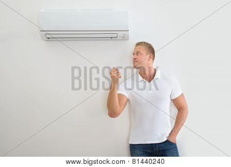 Man With Air Conditioner Remote Control