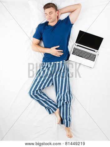 Top view photo of sleeping man with laptop