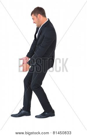 Businessman contorted with hands downt on white background