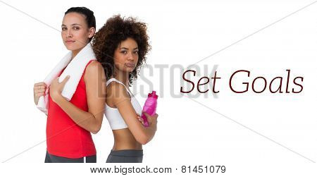 Portrait of two fit young women standing with waterbottle and towel over white background
