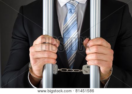 Handcuffed Businessman Holding Bars