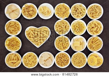 Large pasta food selection in round bowls and in a heart shaped bowl over brown background. poster