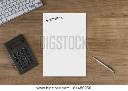 Blank Sheet Businessplan On A Wooden Table With Calculator