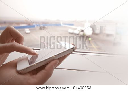 Woman using smart phone by the window at aiport