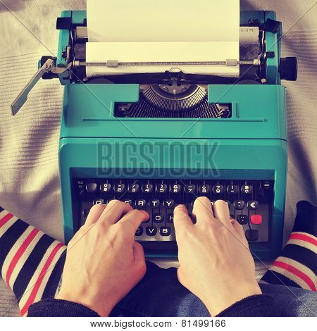 a young man typing in an old typewriter on the bed, with a retro effect