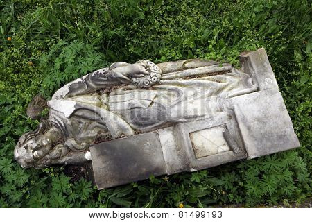 Fallen angel. Destroyed tombstone at the abandoned cemetery in Terezin, Czech Republic.