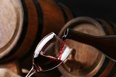 Pouring red wine from bottle into glass with wooden wine casks on background poster
