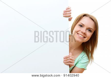 Smiling woman emerging from behind corner