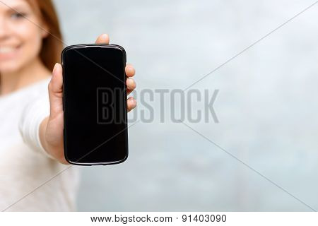 Smiling woman showing he mobile phone