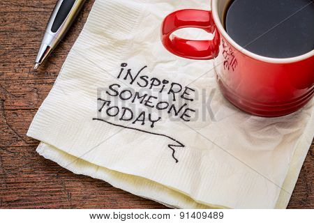 inspire someone today - motivational handwriting on a napkin with cup of coffee
