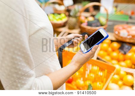 sale, shopping, consumerism and people concept - close up of young woman with food basket in market