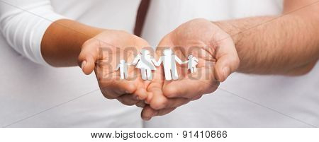 love and relationships concept - closeup of couple cupped hands showing paper man family