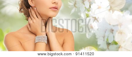 beauty, people and jewelry concept - close up of beautiful woman with pearl earrings and bracelet over summer garden and cherry blossom background