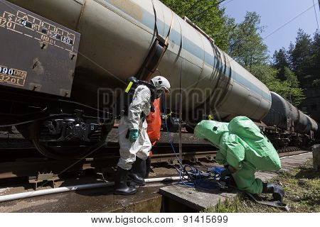 A team working with toxic acids and chemicals is securing a chemical cargo train tanks crashed near Sofia Bulgaria. Teams from Fire department are participating in an emergency training with spilled toxic and flammable materials. poster