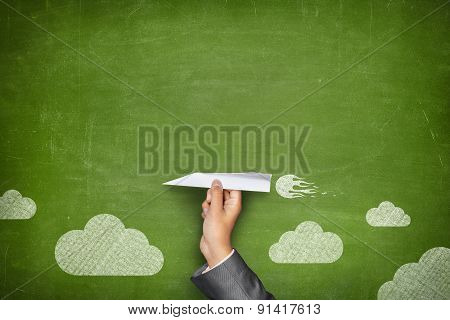 Black blank blackboard with hand holding paper plane