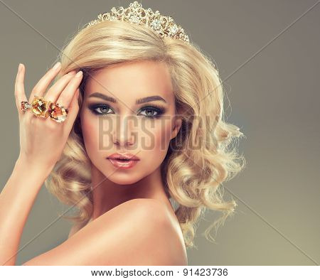 Beautiful cute girl with blonde curly hair with  the tiara on her head and large rings on her  hand