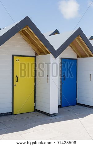 Colourful Doors Of Yellow And Blue, With Each One Being Numbered Individually, Of White Beach Houses