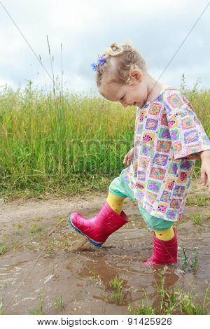 Two years old preschooler girl having fun walking summer field puddle